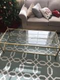 Glass coffee table with gold colored trim