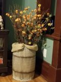 Antique nail keg with hobby lobby flowers and light up branches