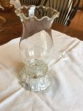 Antique candlestick holder with hurricane lamp.