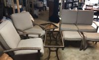 7 piece metal/glass patio furniture with tan cushions and tan covers.