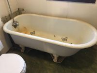 Old antique claw foot bathtub with faucets and shower curtain holder