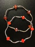 STRETCH BRACELETS (2) ORANGE CLEAR IRIDESCENT/OPAQUE FACETED STONES.