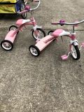 Two pink Radio Flyer tricycles