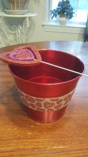 red bucket planter with heart plant stick