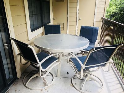 Round glass top patio table and rocking chairs