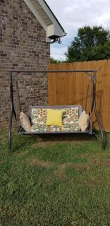 Outdoor swing with new seat cushions. Throw pillows faded except yellow is good