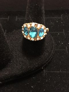 Gold colored ring with aqua and clear colored stones