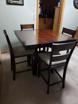 Pub style table with 4 upholstered chairs.