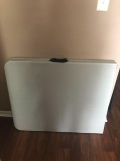 Long folding table that folds in half and has carrying handle