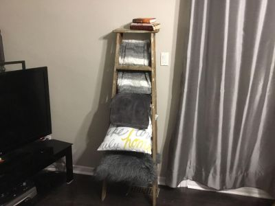 Old wooden rustic ladder perfect for blanket rack and throw pillows.
