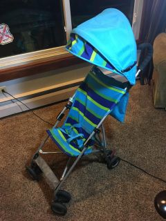 Blue striped umbrella stroller with canopy and storage basket