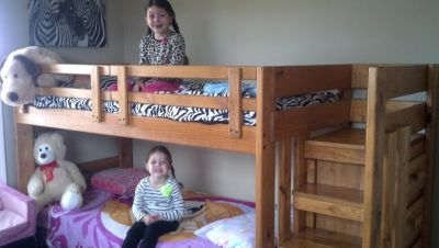 Bunk bed with mattresses and built in dresser under stairs