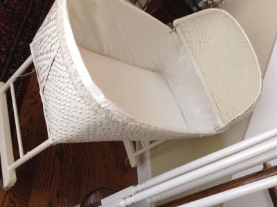 Baby bassinet on wheels and with lace covering.