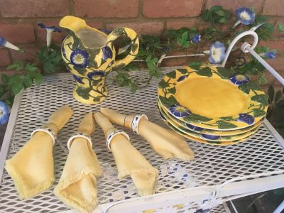 4 plates, 4 napkin rings with yellow cloth napkins, and pitcher.