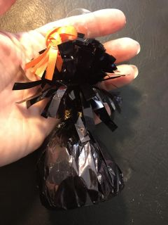 Black balloon weight with a piece of orange ribbon but you can remove that