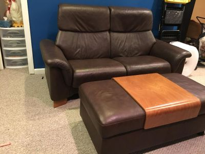 Ekornes reclining loveseat and footstool in brown leather.