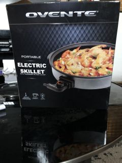 Portable electric skillet with glass cover.