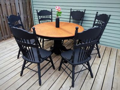 Beautiful refinished Solid Oak Black Clawfoot Pedestal table and 6 ornately detailed hand carved solid Oak chairs with matching leaf.
