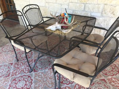 Metal table with chairs and cushions