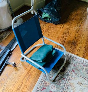 Collapsible blue stadium seat with green fleece blanket