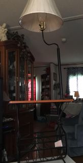 Floor lamp with table attached. It has a magazine rack under table.