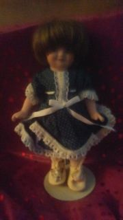 8 inch Porcelain doll with stand. Has shoes, stockings and dress in very good condition!