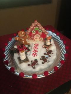 Precious decor for your table! Silver tray decorated with a house, gingerbread man, snowman sitting on a snore, and 3 gingerbread cookies.