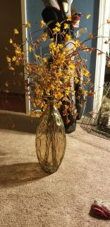 Very gorgeous light brown vase with beautiful floral arrangement.