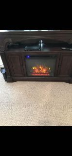 Tv entertainment stand with built in fire place.