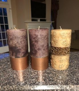 3- 3 x6 decorative pillar candles. One of the taupe brown & copper bottom candles fell & has smush, check next pic. I turn it to face back.