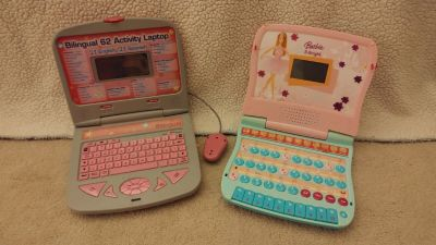 Two little girls play laptops