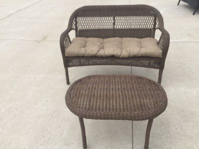 Light brown rattan loveseat with table