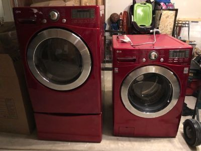 LG red front load washer dryer set with pedestals