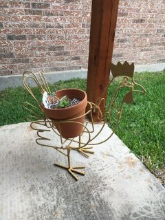 Yellow wrought iron chicken with plant