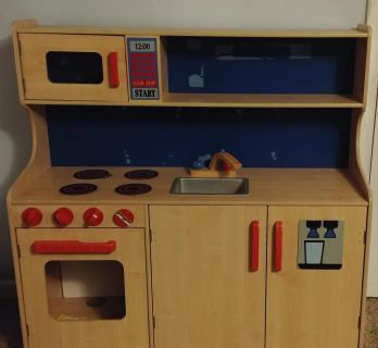 Wooden play kitchen. Has a broken knob and is missing the plastic from the over door. Still lots of fun.