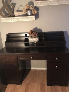Essresso colored desk with removable top . Has plenty of storage and has a file as well as a cabinet .