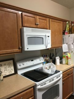 In cabinet above stove white GE Microwave