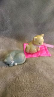 Loving family tan cat with ribbon on and a barbie grey cat, plus a small.pink rug.