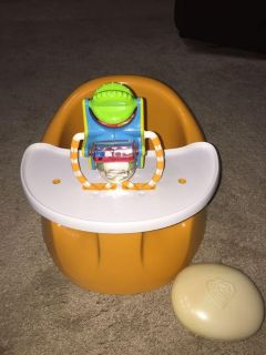 Orange Prince Lionheart seat.Has a tray with toy that is adjustable on a track. Converts to seat only with a knob that attaches to center.