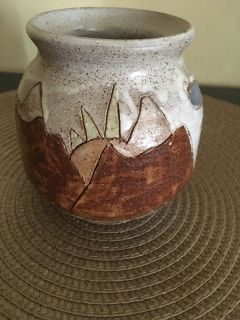 Handmade pottery with mountains, sun, clouds