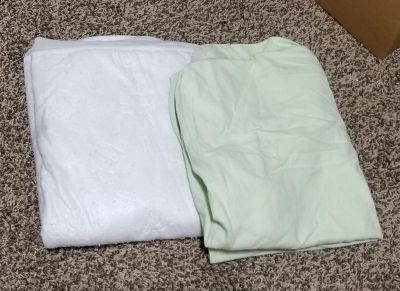 Waterproof mattress protector and light green fitted sheet, both for crib mattresses