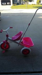 Pink and white tricycle with basket and handle