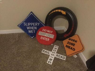 3 road theme throw pillows, round plastic tire wall hanging and Rail Road Crossing wall decor, $3.00 takes all, light wear, nothing crazy.