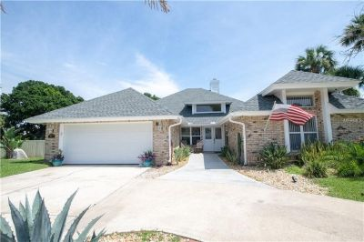 Stunning single family brick home, 2 car garage with a screened in lanai on a corner lot w/ a canal.