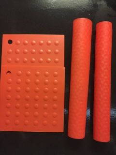 Red silicone baking mats and pot holders
