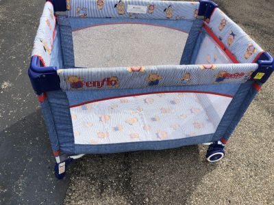 Pack n play with big wheels and toy storage bag on side