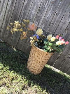 Tall wicker laundry basket full of tall floral arrangements with tags