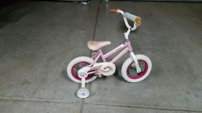 GIRLS BIKE WITH TRAINING WHEELS (those are gray clouds with rain drops on the seat)