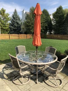 "63"" round glass outdoor patio table and 6 rocking/swivel chairs with umbrella"
