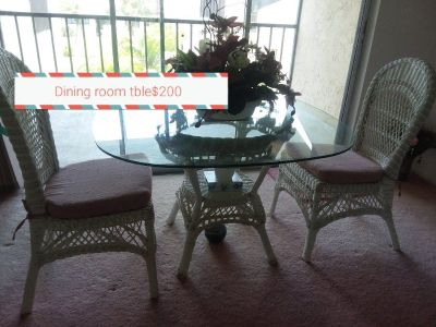 A dining room table white wicker with 4 chairs.